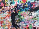Trying to reach John Lennon at the John Lennon Wall in Prague, Czech Republic