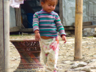 A Nepali child plays just outside of her home