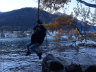Swinging on a hanging tire in Queenstown over the lake