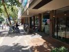The sidewalk alongside the school has plenty of cafes to choose from