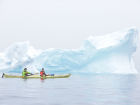 Explorers kayaking through the icebergs